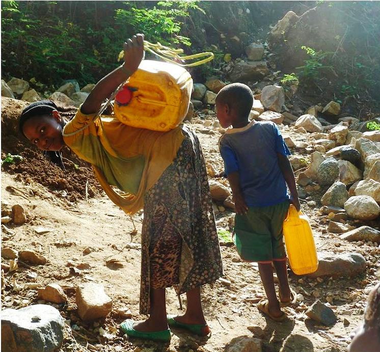 I ragazzi del villaggio portano l'acqua a casa, dopo averla attinta dall'attuale fonte disponibile, sulla cima di una ripida collina. - aspettando il nuovo sistema di pozzi.
